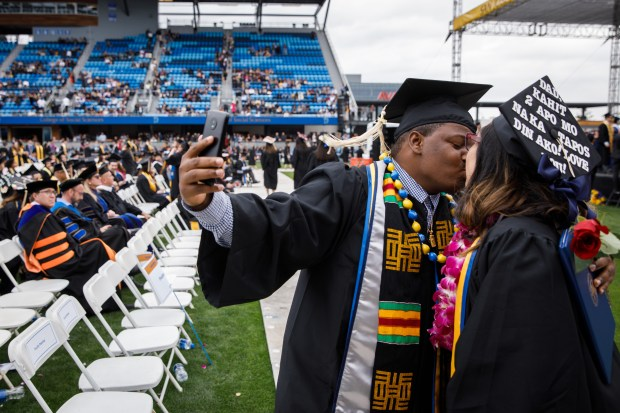 San Jose State University graduate Dontae Lartigue kisses his wife, Katherine, who is also graduating, during a graduation ceremony on May 24, 2018, at Avaya Stadium in San Jose. (Dai Sugano/Bay Area News Group)