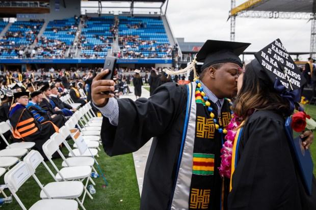 San Jose State University graduate Dontae Lartigue kisses his wife, Katherine, who is also graduating, during a graduation ceremony on May 24, 2018, at Avaya Stadium in San Jose. (Dai Sugano/Bay Area News Group)