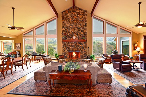 Windows on either side add to the drama of the floor-to-ceiling river rock fireplace.
