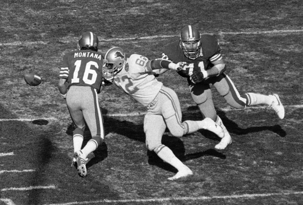 Detroit defensive end Curtis Green (62) gets a hand on 49ers quarterback Joe Montana (16 )who coughs up the ball in first quarter action at San Francisco, Dec. 31, 1983. San Francisco's Randy Cross recovered. At right is 49ers Keith Fahnhorst (71). (AP Photo/Mark Costantini)