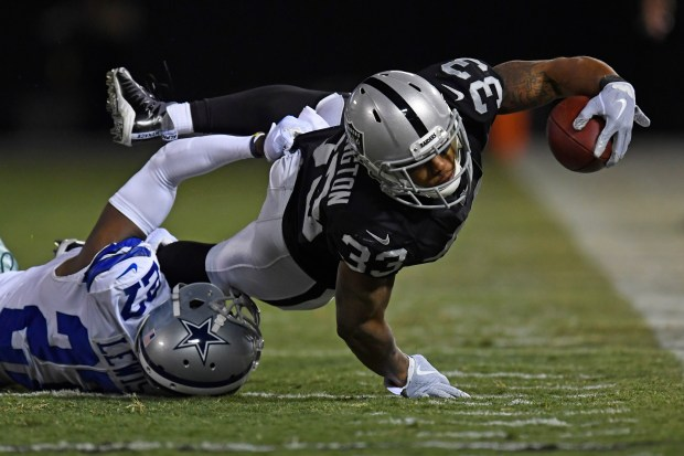 Oakland Raiders' DeAndre Washington (33) stretches for extra yardage after being tackled by Dallas Cowboys' Jourdan Lewis (27) in the second quarter of their NFL game at the Coliseum in Oakland, Calif. on Sunday, Dec. 17, 2017. (Jose Carlos Fajardo/Bay Area News Group)