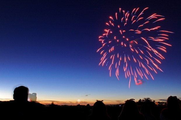 A man stops to take a photograph of the Fourth of July fireworks at the Martinez Regional Shoreline in Martinez, Calif., on Thursday, July 4, 2014. (Jose Carlos Fajardo/Bay Area News Group archive)