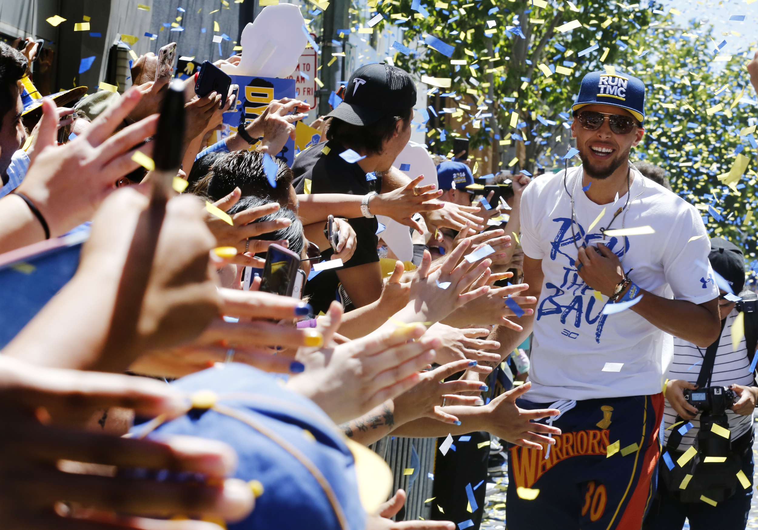 Stephen Curry makes his way down the a line of fans giving high fives during the Warriors Championship parade in Oakland Calif.