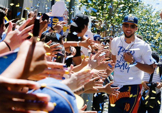 Stephen Curry makes his way down the a line of fans giving high fives during the Warriors Championship parade in Oakland, Calif., on Tuesday. June 12, 2018.  (Laura A. Oda/Bay Area News Group)
