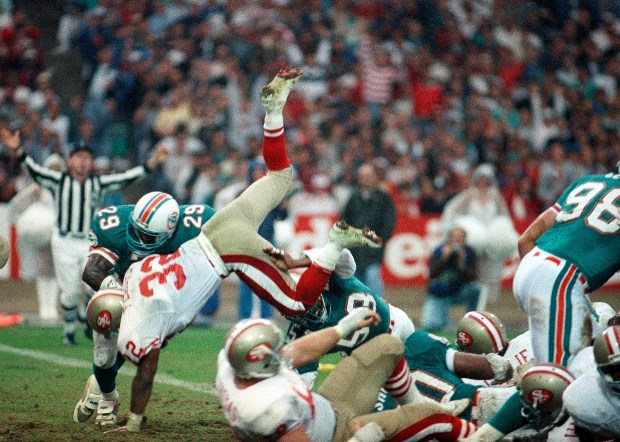 San Francisco 49ers running back Terrence Flagler flies over the top to touchdown in the end zone for a penalty call just before halftime, Sunday, July 31, 1988 against the Miami Dolphins London's Wembley Stadium, during the annual American Football Exhibition match. Number 29 for the Dolphins is Liffort Hobley. (AP Photo)