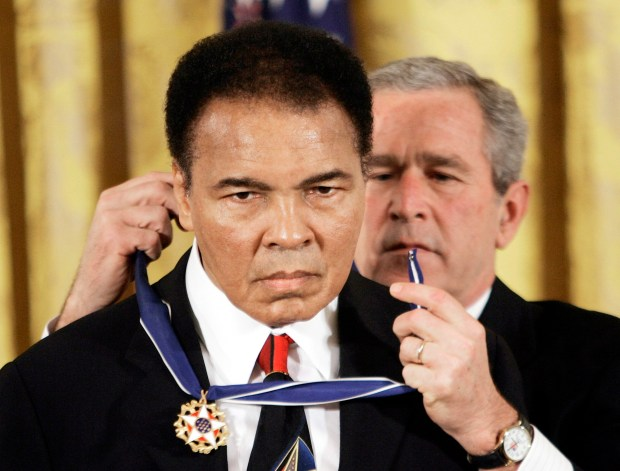 """FILE - In this Nov. 2009 file photo, President Bush presents the Presidential Medal of Freedom to boxer Muhammad Ali in the East Room of the White House. President Donald Trump said he is thinking """"very seriously"""" about pardoning Muhammad Ali, even though the Supreme Court vacated the boxing champion's conviction in 1971. (AP Photo/Evan Vucci)"""