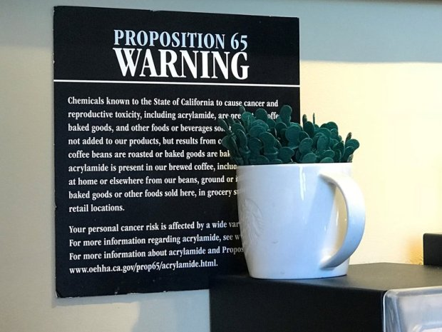 In this March 30, 2018, file photo, a posted Proposition 65 warning sign is seen on display at a coffee shop in Burbank, Calif. State health officials proposed a regulation change Friday, June 15, 2018, that would declare coffee doesn't present a significant cancer risk, countering a recent California state court ruling that had shaken up some coffee drinkers. (AP Photo/Damian Dovarganes, File)