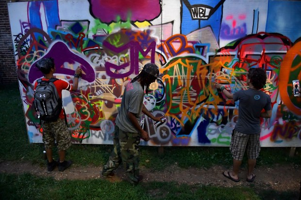"From left, Kahlil Potter, Amir Frost and Andres Paredes Vincent hone their skills as graffiti artists on a practice wall where old-school graffiti artist Asad ""Ultra"" Walker teaches art in Washington, D.C. MUST CREDIT: Washington Post photo by Katherine Frey"