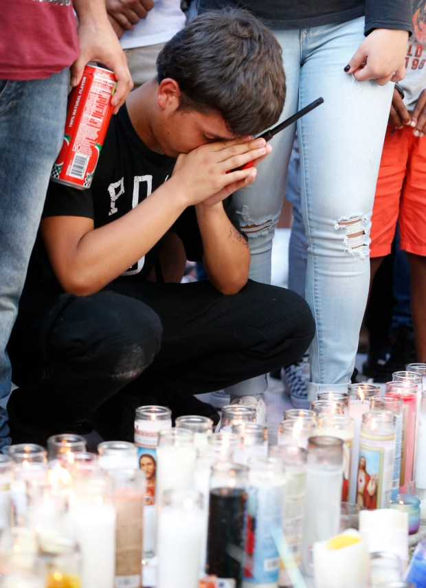 A mourner of rapper XXXTentacion pauses at a memorial, Tuesday, June 19, 2018, outside Riva Motorsports in Deerfield Beach, Fla., where the troubled singer was killed the day before. The 20-year-old rising star, whose real name is Jahseh Dwayne Onfroy, was shot and killed Monday in Florida in what police called an apparent robbery attempt. (AP Photo/Wilfredo Lee)