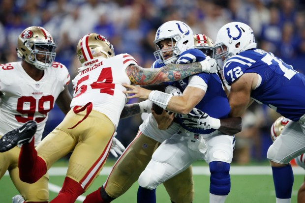 6ee32c8176d ... gets sacked by Jeremiah Attaochu  92 and Cassius Marsh  54 of the San  Francisco 49ers in the first quarter of a preseason game at Lucas Oil Stadium  on ...