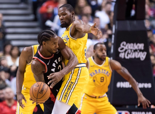 6e6b25d46ce Toronto Raptors forward Kawhi Leonard (2) moves the ball around Golden  State Warriors forward Kevin Durant during overtime in an NBA basketball  game ...