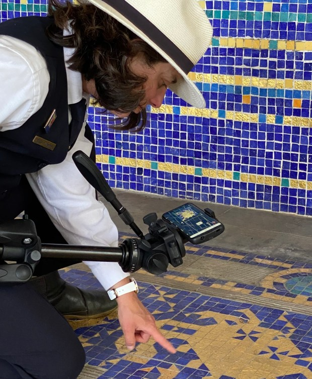 Hearst Castle tour guide Tracy Kosinski points to gold-infused glass tiles at the indoor Roman Pool.