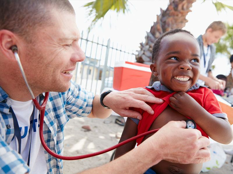 Older Man Using A Stethoscope On Young Boy