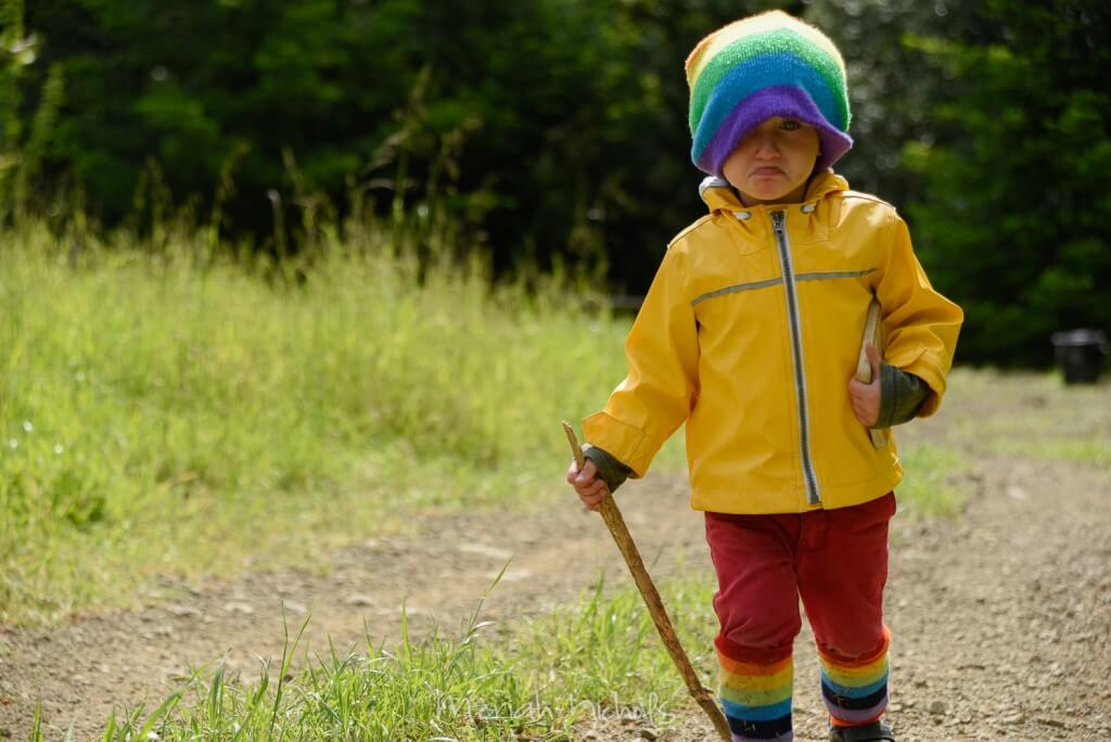 Mack - wearing a a yellow raincoat, rainbow hat and rainbow socks - approaches, with his walking stick in one hand and his Dr Seuss book in the other. His mouth is perfectly downturned and he is ready to cry