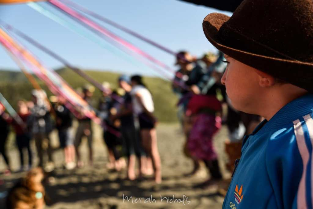 small boy watches maypole dance