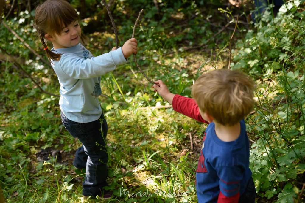 two kids mock fighting with sticks