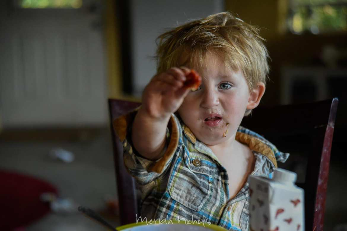 small boy holding up a sundried tomato in apparent disgust and outrage