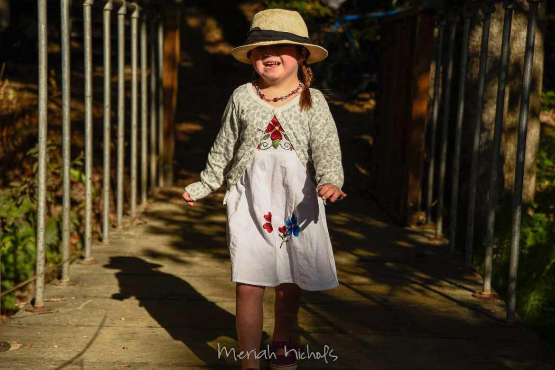 little girl walks forward, smiling broadly