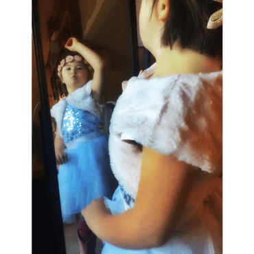"child with flower headband and sparkly dress has her arm lifted in tribute to the song, ""let it go"""
