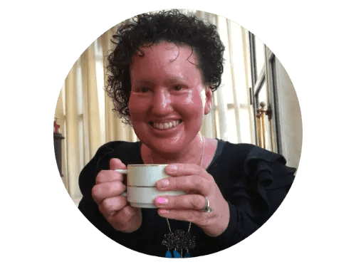 Carly Findlay: blogger, appearance activist. Image is of a woman holding a cup, smiling broadly. She has curly brown hair and pink skin.