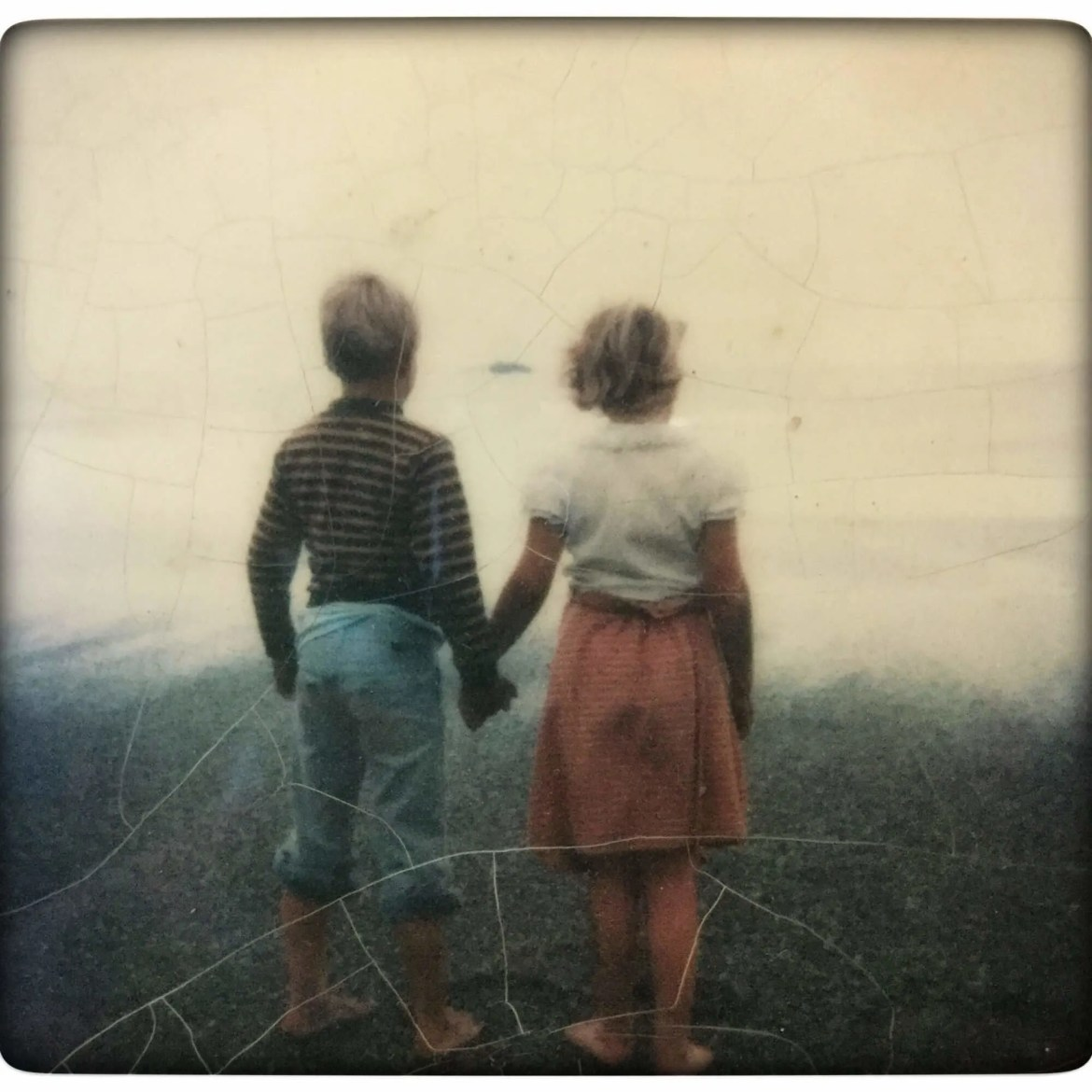 two children hold hands while facing the sea