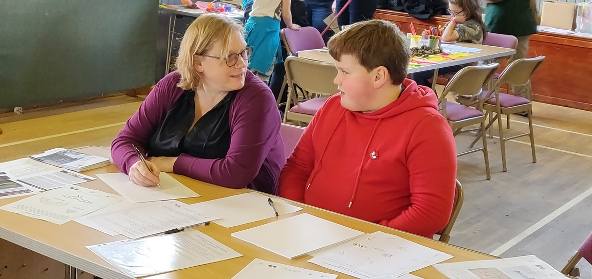 Mother and son work together on a writing activity