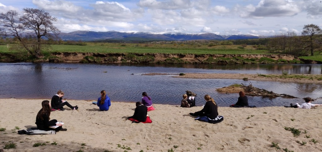 Pupils doing creative writing exercise beside River Spey, Highlands of Scotland