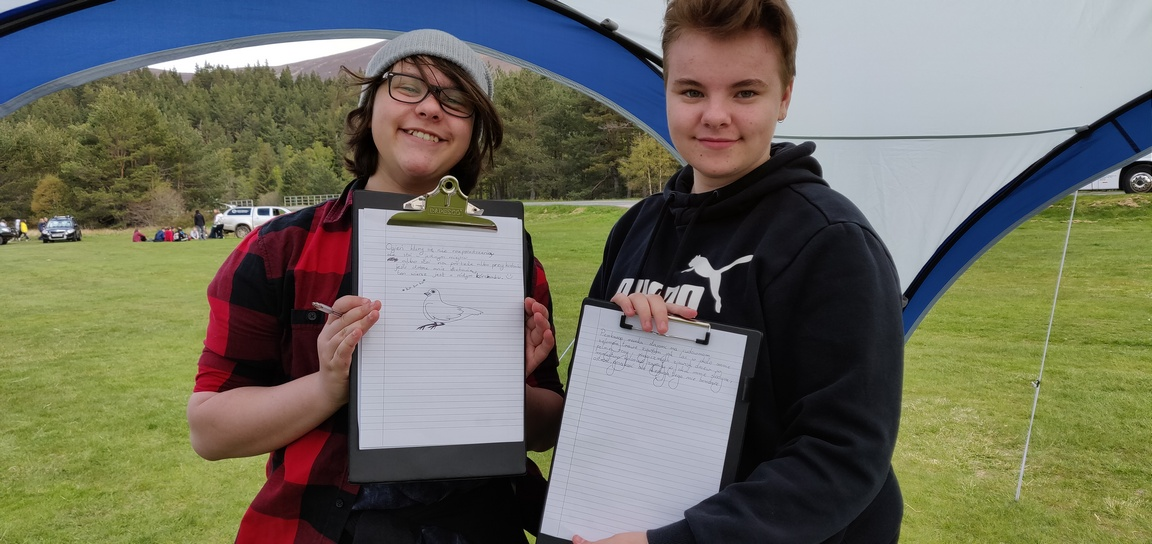 Two teenage girls show their poems on clipboards