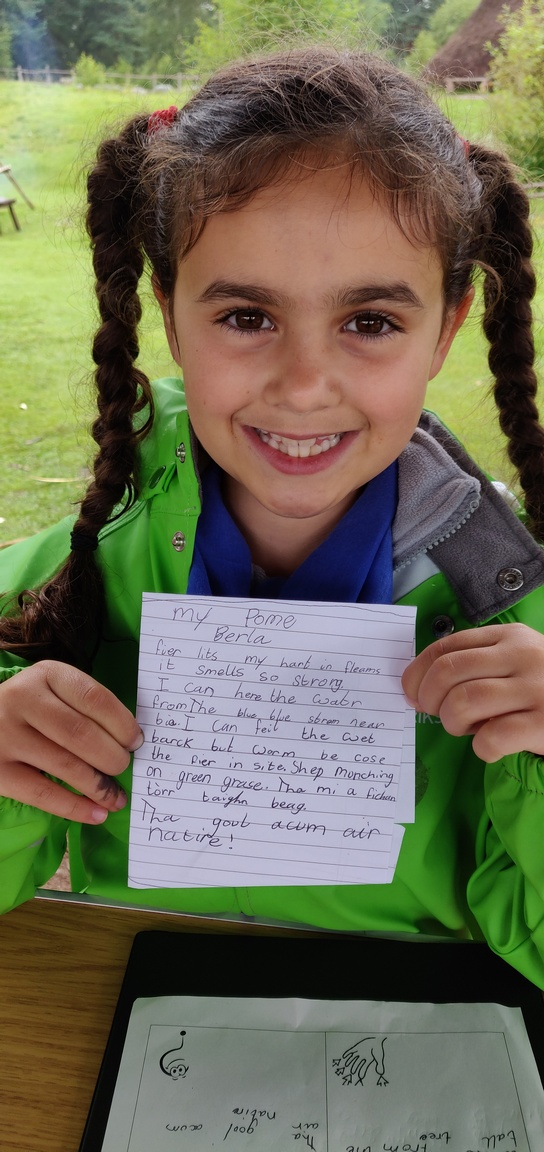 A smiling girl holds her poem written in English and Gaelic