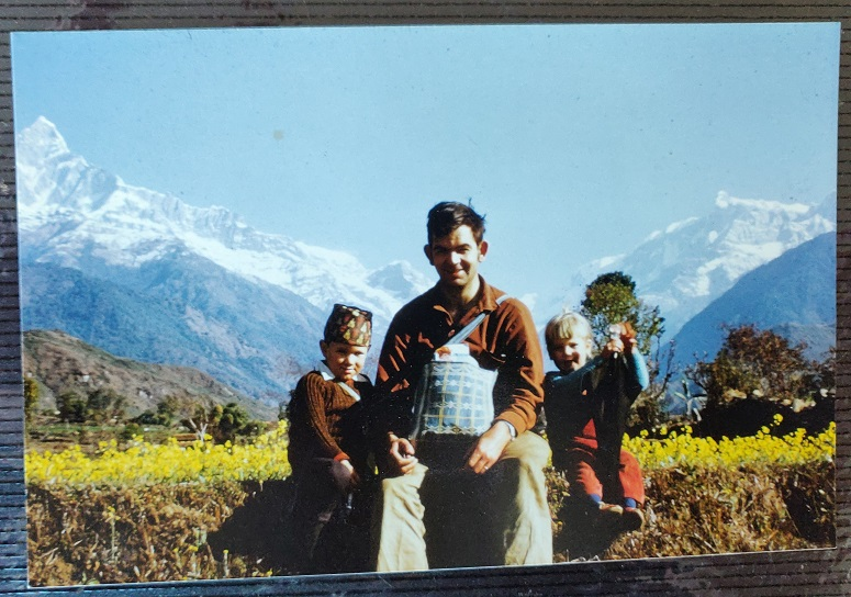 Man & children sitting in a field with mountains behind