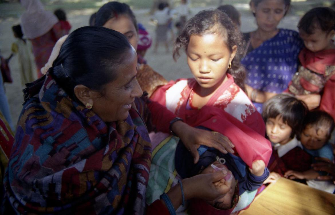 Woman giving polio vaccine to a child