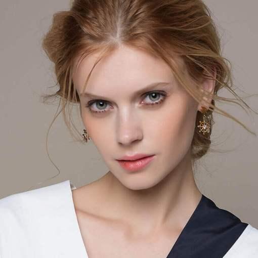 boucles oreilles gouvernail plaque or portes par une femme