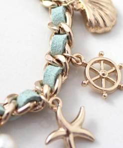 Bracelet série de coquillages et mer focus sur gouvernail
