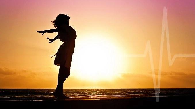 Mujer tomando una respiración profunda con los brazos abiertos en la playa con el sol y el mar de fondo.  Latido discreto que se integra con el entorno.