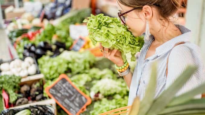 Puesto en el mercado de frutas y verduras con persona de compras