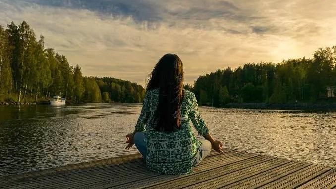 Mujer sentada con las piernas cruzadas frente a un paisaje natural (lago, bosque, puesta de sol).  Salud, bienestar y relajación.