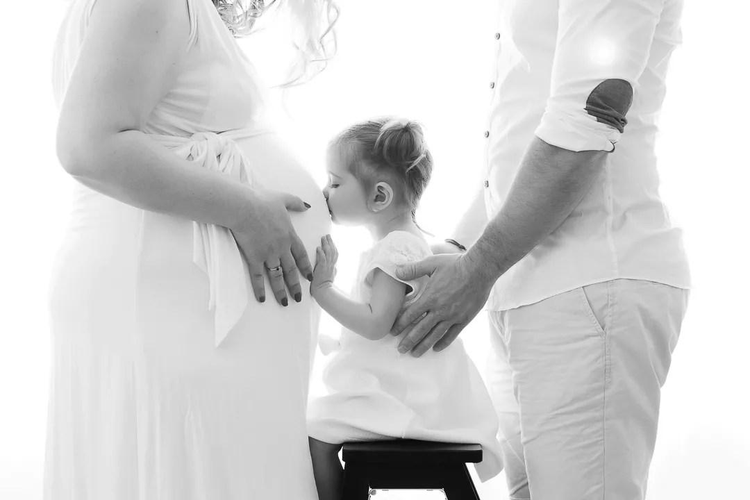 photo famille pendant la grossesse bébé bisous ventre future maman en noir et blanc