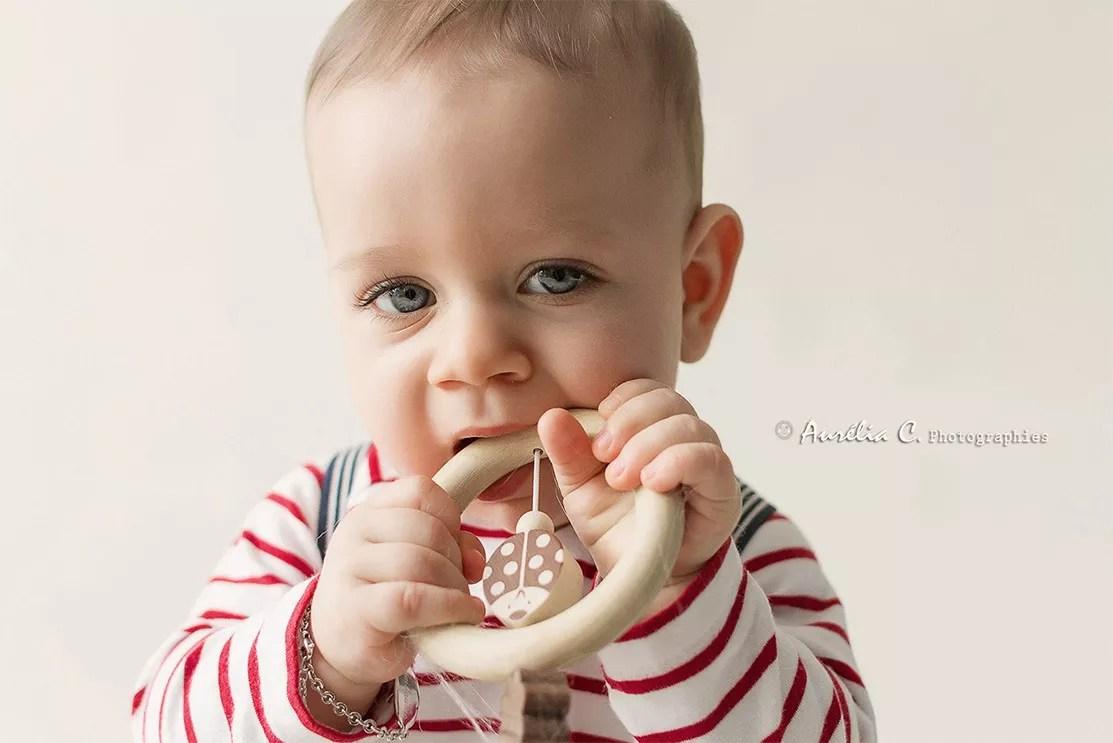 portrait bébé mord son hochet en bois