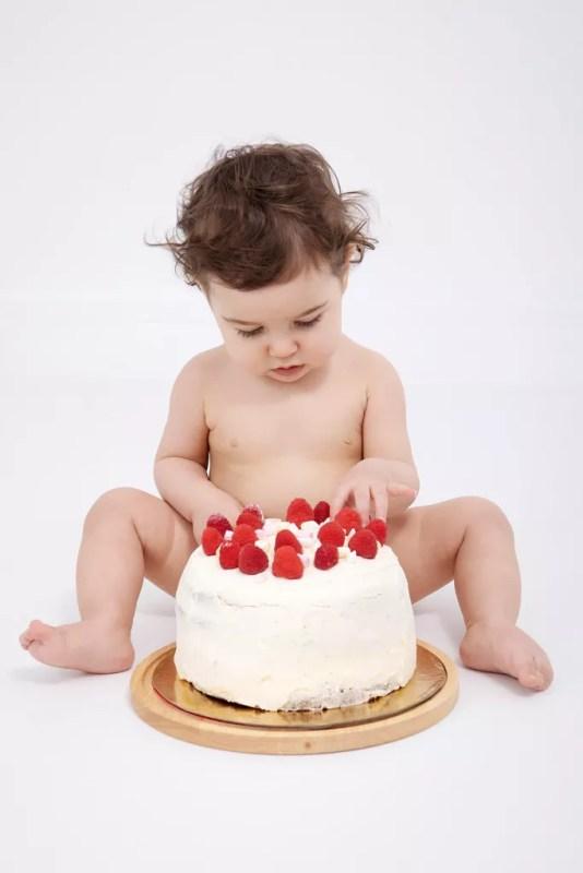 bébé qui découvre son gâteau d'anniversaire avec des framboises