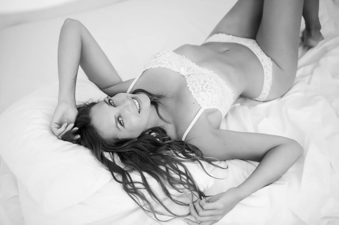 portrait femme dans lit à baldaquin séance photo boudoir en lingerie blanche