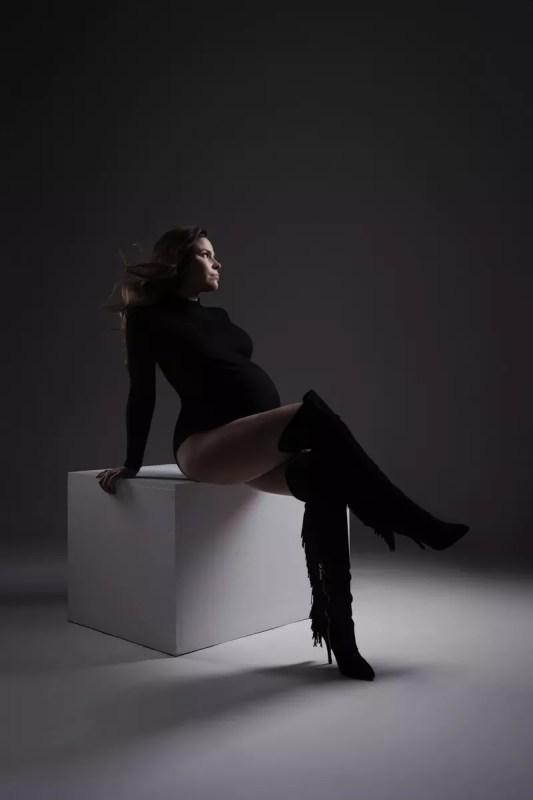 séance grossesse glamour pose assise sur cube blanc en body et cuissardes