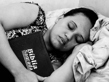 Woman sleeping with Bible in arms