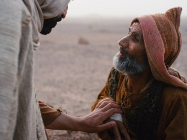 Jesus touching a man's hand with leprosy