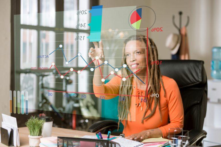 African American woman viewing a futuristic virtual financial chart