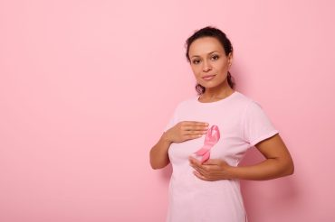 African American woman puts hands around pink ribbon on her pink T Shirt, for breast cancer campaign, supporting Breast Cancer Awareness. Concept of 1 st October Pink Month and women's health care