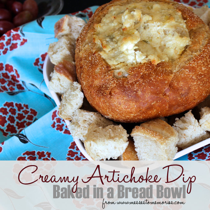 A creamy artichoke dip baked into a bread bowl from Messes to Memories