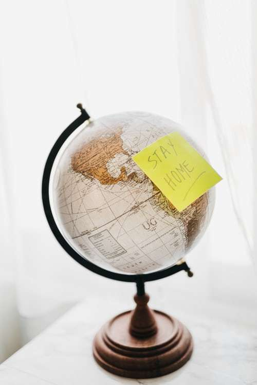 Globe with a stay at home sign