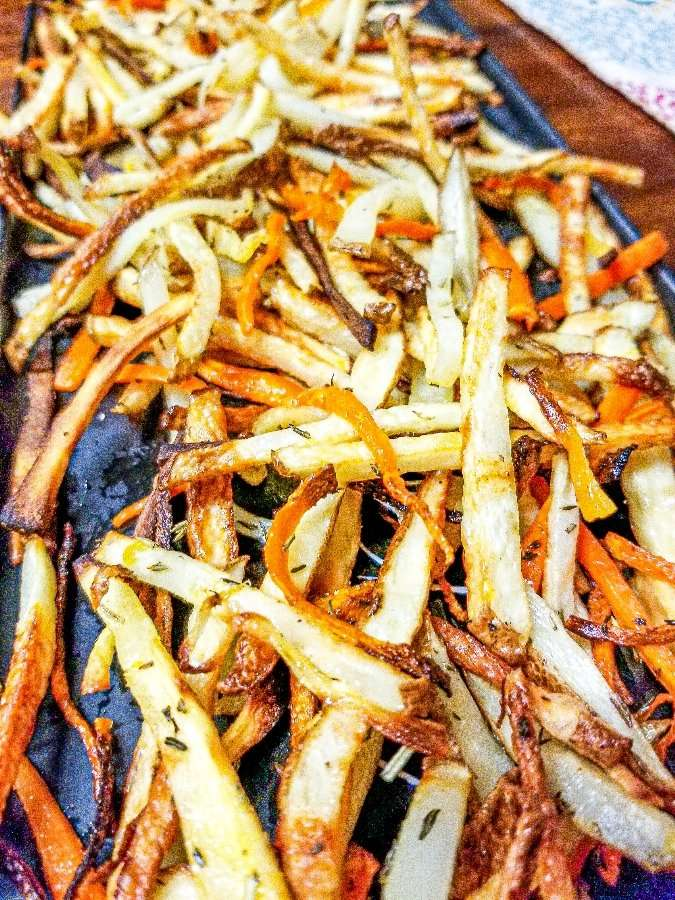 A plate loaded with parsnip carrot fried that have been air fried.