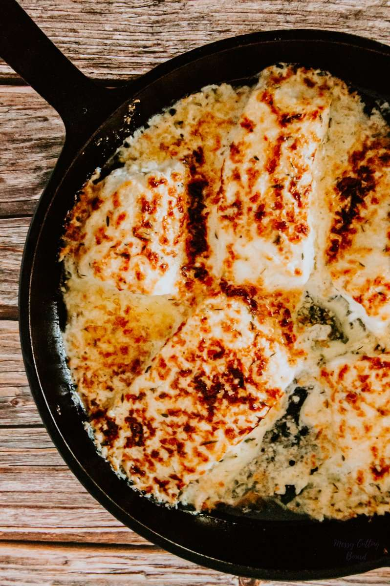 A cast-iron pan full of Parmesan Lemon-Herb Baked Halibut straight out of the oven.