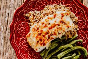A fillet of Lemon-Herb Baked Halibut served on a plate with wild rice and fresh green beans